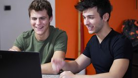 Young men videochatting on laptop PC stock footage