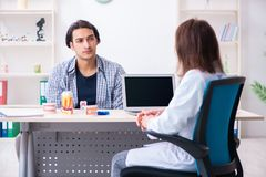 Young man visiting female doctor stomatologist. The young men visiting female doctor stomatologist royalty free stock photography