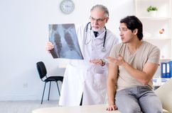 The young man visiting old male doctor radiologist royalty free stock image
