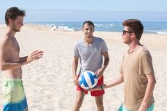 Young men with volleyball playing volley on beach Stock Photos