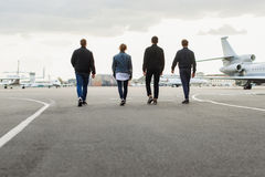 Young men walking on airfield Stock Images