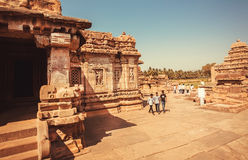 Young men walking past ancient Hindu temple with monumental sculptures Royalty Free Stock Images