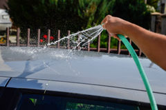 Young men washing silver car with pressured water and brush at sunny day. Close up of cleaning car on summer time Royalty Free Stock Photography