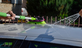 Young men washing silver car with pressured water and brush at sunny day. Close up of cleaning car on summer time Stock Images