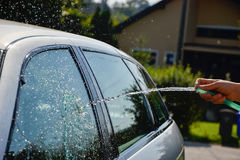 Young men washing silver car with pressured water and brush at sunny day. Close up of cleaning car on summer time. Taking care of the car. Man cleaning modern Stock Images