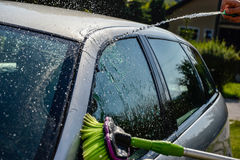 Young men washing silver car with pressured water and brush at sunny day. Close up of cleaning car on summer time Stock Photo