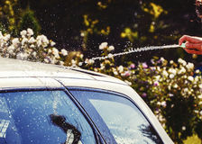 Young men washing silver car with pressured water and brush at sunny day. Close up of cleaning car on summer time. Taking care of the car. Man cleaning modern Royalty Free Stock Image