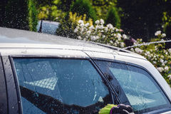 Young men washing silver car with pressured water and brush at sunny day. Close up of cleaning car on summer time. Taking care of the car. Man cleaning modern Royalty Free Stock Photography