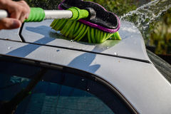 Young men washing silver car with pressured water and brush at sunny day. Close up of cleaning car on summer time Royalty Free Stock Photos
