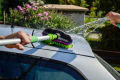 Young men washing silver car with pressured water and brush at sunny day. Close up of cleaning car on summer time. Taking care of the car. Man cleaning modern Stock Photography