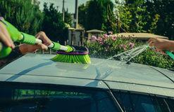 Young men washing silver car with pressured water and brush at sunny day. Close up of cleaning car on summer time Royalty Free Stock Images