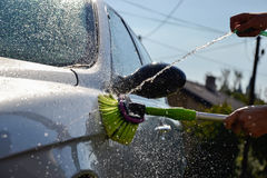 Young men washing silver car with pressured water and brush at sunny day. Close up of cleaning car on summer time Royalty Free Stock Photo