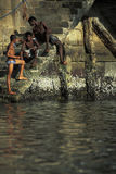 Young men washing themselves in the harbor, Salvador, Brazil. Royalty Free Stock Images