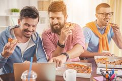Young Men Watching into Laptop and Eating Pizza. Three Young Men Watching into Laptop and Eating Pizza. Friendship Concept. Man Using Digital Device. Men with royalty free stock photos