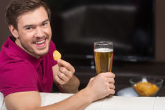 Young men watching TV. Cheerful young men smiling at camera while sitting in front of TV and holding beer glass. Young man watching TV. Cheerful young man royalty free stock photo