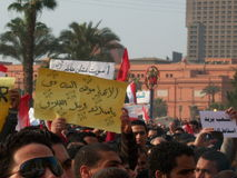 Egyptian revolution. People protesting in the Tahrir square in Egypt during the Egyptian revolution in the Arab Spring. The Egyptian museum in the background Stock Images