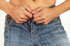 Young men wear his blue jeans closeup. Young men wear his blue jeans close up Royalty Free Stock Photography