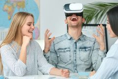 Young couple in a tour agency communication with a travel agent travelling concept virtual reality headset impressed. Young men wearing virtual reality headset Royalty Free Stock Photography