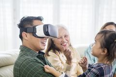 Young man wearing VR headset with his family. Young men wearing VR headset with his family at home while sitting on the sofa royalty free stock image