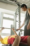 Young men weight lifting with his personal trainer in the gym Royalty Free Stock Images