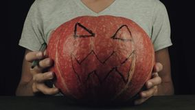 Young men in white t-shirt draws scary face on pumpkin with a marker stock video footage