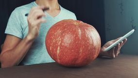 Young men in white t-shirt use tablet computer and examine pumpkin in front of him 4k stock footage