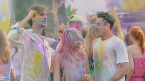 Young men and woman covered in holi festival colors dancing to music, slow-mo. Stock footage stock video