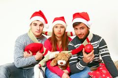 Young men and woman with Santa Claus hats Stock Image
