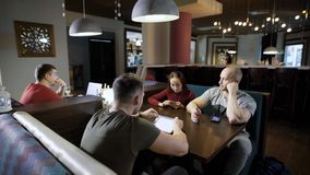Group of friends in cafe using gadgets. Young men and woman sitting in modern cafeteria all using and watching devices stock footage