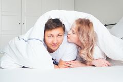 Young men and woman under blanket together. Young men and women under blanket together, white bedroom, smiling couple Royalty Free Stock Photo