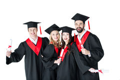 Young men and women in academic caps holding certificates and smiling. Happy young men and women in academic caps holding certificates and smiling royalty free stock images