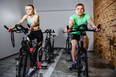 Young man and woman biking in the gym, exercising legs doing cardio workout cycling bikes. Young men and women biking in the gym, exercising legs doing cardio Royalty Free Stock Images