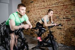 Young man and woman biking in the gym, exercising legs doing cardio workout cycling bikes. Young men and women biking in the gym, exercising legs doing cardio Royalty Free Stock Image