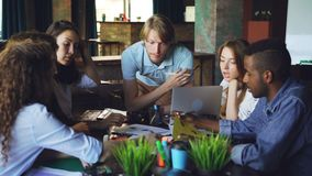 Young men and women colleagues are looking at papers lying on table and talking sharing ideas. Teamwork, modern office. Information and company employees stock footage