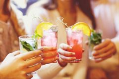 Young men and women drinking cocktail at party. Close up royalty free stock photography