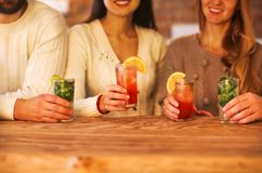 Young men and women drinking cocktail at party Stock Photos