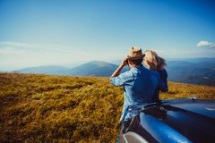 Romantic trip to the mountains. The young men with the women is far away in the mountains looking at the Carpathian Mountains through binoculars Stock Photo
