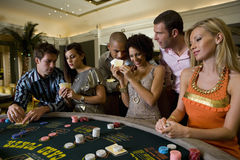 Young men and women gambling at poker table in casino, smiling Royalty Free Stock Image