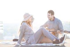 Young man and woman with guitar having fun outdoors Stock Photos