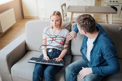 Young man and woman have social media addiction. Sitting on sofa. Hostages. Emotionless woman on sofa. Worried man stock photo