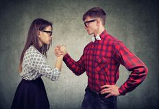 Man and woman in rivalry. Young men and women having competition in arm wrestling looking at each other in domination stock images