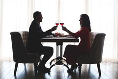 Young couple having romantic dinner in the restaurant toast holding hands. Young men and women having romantic dinner in the restaurant drinking wine cheers stock photos