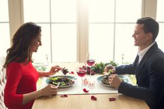 Young couple having romantic dinner in the restaurant enjoying food. Young men and women having romantic dinner in the restaurant eating salad enjoying food Royalty Free Stock Photo
