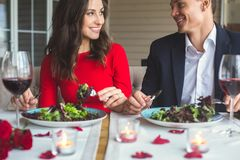 Young couple having romantic dinner in the restaurant eating talking. Young men and women having romantic dinner in the restaurant eating salad smiling talking Royalty Free Stock Image