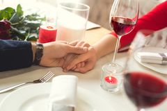 Young couple having romantic dinner in the restaurant holding hand drinking close-up. Young men and women having romantic dinner in the restaurant holding hand Stock Images