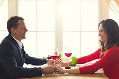 Young couple having romantic dinner in the restaurant holding hands smiling. Young men and women having romantic dinner in the restaurant holding hands drinking Stock Photography