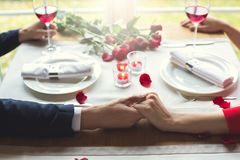 Young couple having romantic dinner in the restaurant sitting holding hands close-up. Young men and women having romantic dinner in the restaurant sitting royalty free stock images