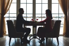 Young couple having romantic dinner in the restaurant holding hands. Young men and women having romantic dinner in the restaurant sitting smiling looking on each Royalty Free Stock Images