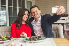 Young couple having romantic dinner in the restaurant sitting taking photos. Young men and women having romantic dinner in the restaurant sitting taking selfie Royalty Free Stock Images