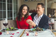 Young couple having romantic dinner in the restaurant sitting together holding hand. Young men and women having romantic dinner in the restaurant sitting Stock Photos
